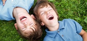 brothers lying in grass laughing