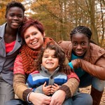 Foster carer with three foster siblings in wooded area