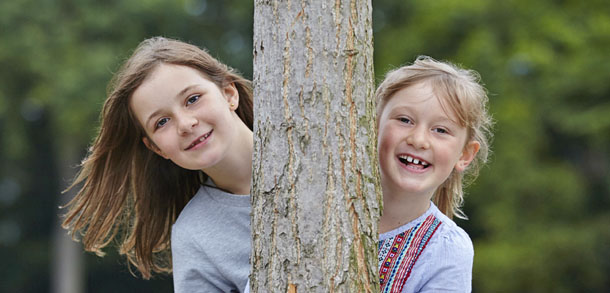 Sisters peer out from behind a tree-trunk, perhaps playing hide and seek