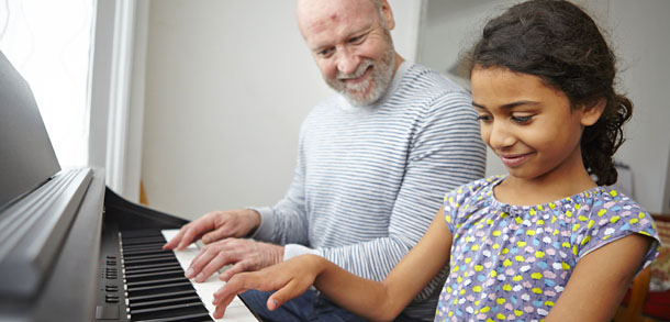 Adoptive father and daughter playing a piano duet
