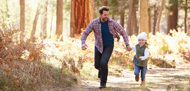 Father and daughter running in autumnal woods