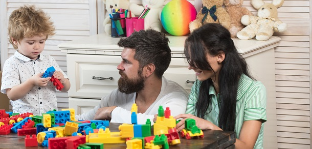 mum and dad playing toy bricks with toddler son
