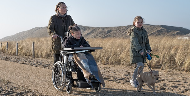 girl in wheelchair out for a walk with family