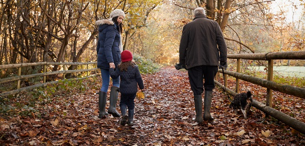 grandad out for autumn walk with daughter and granddaughter