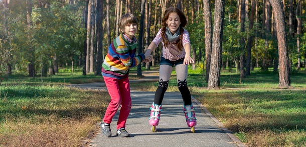 boy supporting girl who is learning to rollerskate