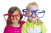 young boy and child wearing red and blue comedy glasses
