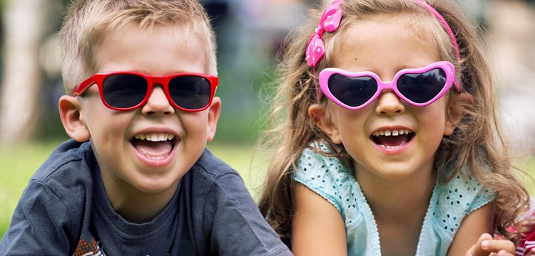 Young boy and girl laying in the grass wearing pink and red sunglasses